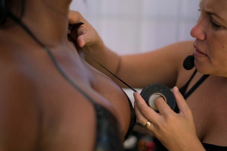 In this Jan. 11, 2017 photo, Erika Martins uses electrical tape to make a customer's bikini at her rooftop salon in the suburb of Realengo in Rio de Janeiro, Brazil. MartinsÕ technique is precise. First she protects womenÕs intimate parts with gauze before covering them with strips of electrical tape, thus creating a tailored Brazilian-style bikini. (AP Photo/Renata Brito)