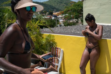 In this Jan. 11, 2017 photo, women tan on the rooftop of the Erika Bronze salon in the suburb of Realengo in Rio de Janeiro, Brazil. The salon applies bikinis made out of black electrical tape directly to the skin, which after an hour of broiling sun get peeled back to reveal crisp tan lines. (AP Photo/Renata Brito)