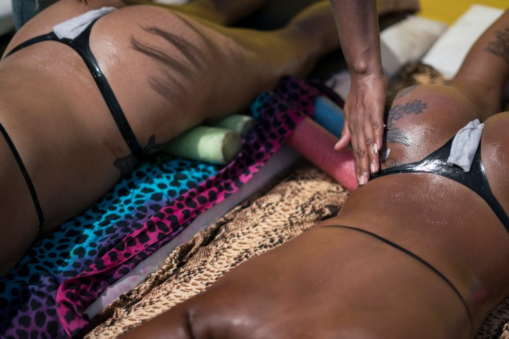 In this Jan. 11, 2017 photo, a salon worker applies sunblock over a customer's tattoos as she tans at the Erika Bronze salon in Rio de Janeiro, Brazil. As summer descends upon the southern hemisphere, some Rio women are swapping the cityÕs postcard beaches for this rooftop tanning salon to get what they call the perfect bikini tan line. (AP Photo/Renata Brito)