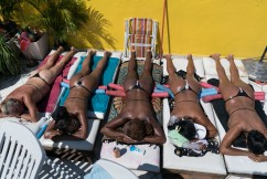 In this Jan. 15, 2017 photo, women tan while wearing bikinis made out of electrical tape on the rooftop of the Erika Bronze salon in the suburb of Realengo in Rio de Janeiro, Brazil. As summer descends upon the southern hemisphere, some Rio women are swapping the cityÕs postcard beaches for this rooftop tanning salon to get what they call the perfect bikini tan line. (AP Photo/Renata Brito)
