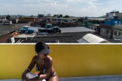 In this Jan. 15, 2017 photo, a woman tans while wearing a bikini made out of electrical tape at the Erika Bronze salon in the suburb of Realengo in Rio de Janeiro, Brazil. As summer descends upon the southern hemisphere, some Rio women are swapping the cityÕs postcard beaches for this rooftop tanning salon to get what they call the perfect bikini tan line. (AP Photo/Renata Brito)