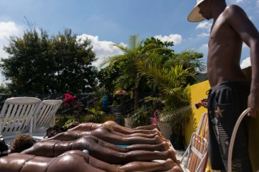 In this Jan. 15, 2017 photo, an employee of the Erika Bronze rooftop salon sprays customers with water as they tan in Rio de Janeiro, Brazil. It is not uncommon for the salonÕs customers to faint or feel dizzy after a rooftop tanning session where temperatures easily go over the 100 Fahrenheit mark in the Rio summer (40 degrees celsius). (AP Photo/Renata Brito)