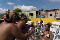 In this Jan. 15, 2017 photo, women chat while tanning at the Erika Bronze salon in the suburb of Realengo in Rio de Janeiro, Brazil. As summer descends upon the southern hemisphere, some Rio women are swapping the cityÕs postcard beaches for this rooftop tanning salon to get what they call the perfect bikini tan line. (AP Photo/Renata Brito)