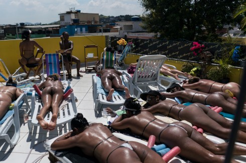 In this Jan. 15, 2017 photo, women tan while wearing bikinis made out of electrical tape at the Erika Bronze salon in the suburb of Realengo in Rio de Janeiro, Brazil. As summer descends upon the southern hemisphere, some Rio women are swapping the cityÕs postcard beaches for this rooftop tanning salon to get what they call the perfect bikini tan line. (AP Photo/Renata Brito)